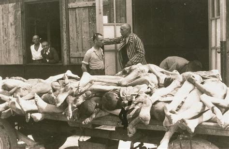 Survivors converse behind a cart loaded with the bodies of